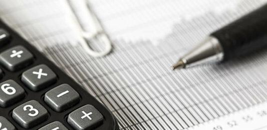 uma calculadora, clips e caneta em cima de um papel com gráficos
