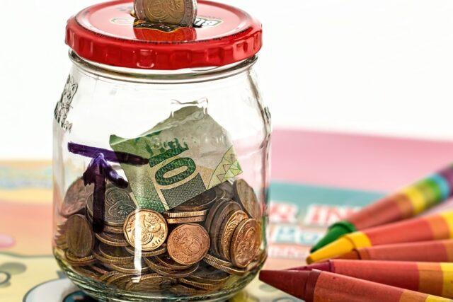 pote com dinheiro e notas dentro e e vários lápis