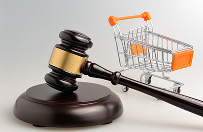 martelo de juiz e um carrinho de supermercado atrás