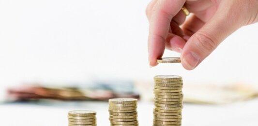 quatro fileiras de moedas com uma mão colocando uma moeda
