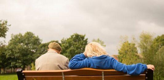 casal de idosos sentados em um banco de madeira na natureza