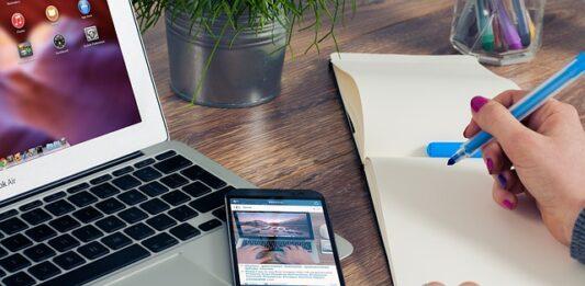 pessoa escrevendo em uma folha com um celular e notebook no lado