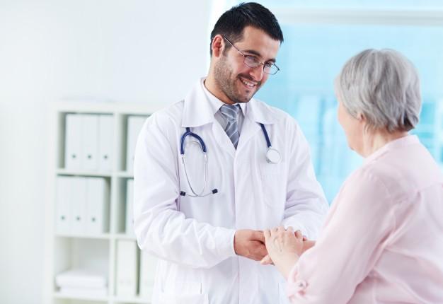 portabilidade plano de saúde: Jovem médico dando as mãos a uma idosa