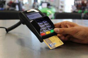 Mão utilizando máquina de cartão de crédito