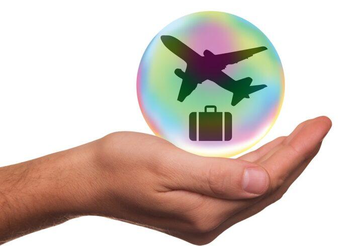 Montagem de uma mão com um círculo e desenho de um avião com uma mala embaixo