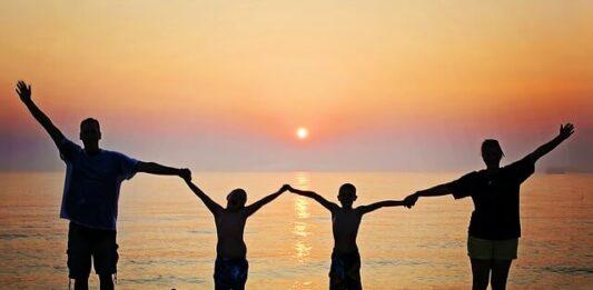família na praia de frente para o mar de mãos dadas vendo o pôr do sol