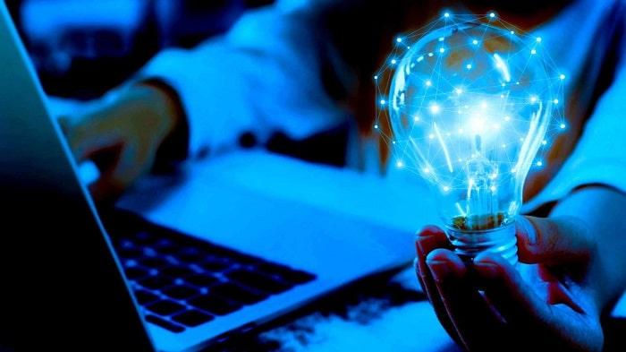 pessoa com uma lâmpada na mão com um laptop