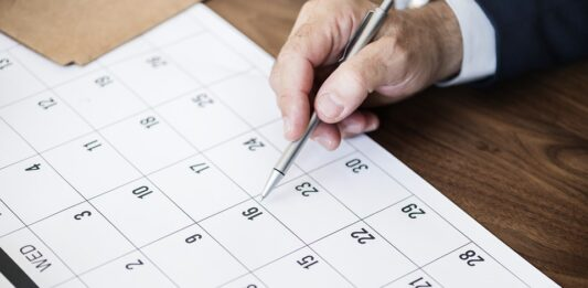 mão apontando com caneta em uma data no calendário