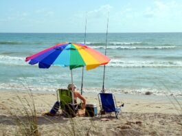 pessoa aposentada sentada na areia da praia