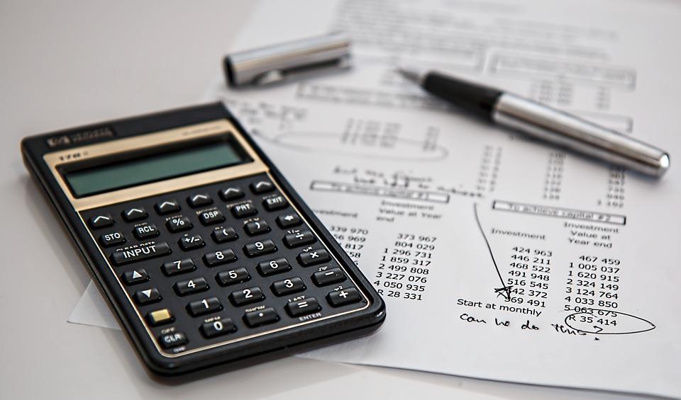 Calculadora, uma caneta e uma folha com valores circulados para ilustrar o texto sobre finanças pessoais
