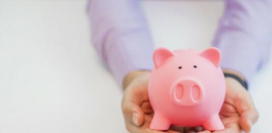 pessoa segurando porquinho rosa para lance no consórcio de dinheiro