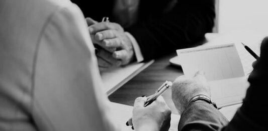 imagem de duas pessoas assinando um contrato de consórcio