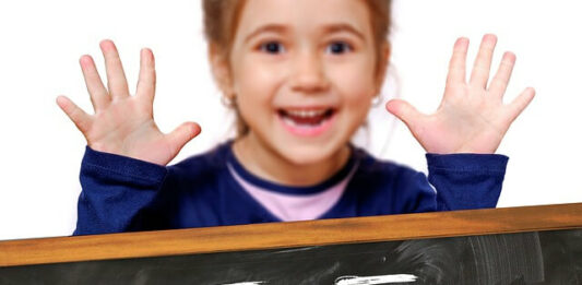 criança feliz com as duas mãos abertas em cima de uma lousa com cálculo (5+5)