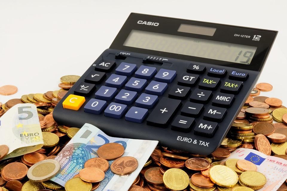 Calculadora posicionada acima de notas e cédulas de dinheiro