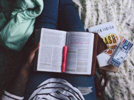 Estudante com livro aberto e uma caneta no meio