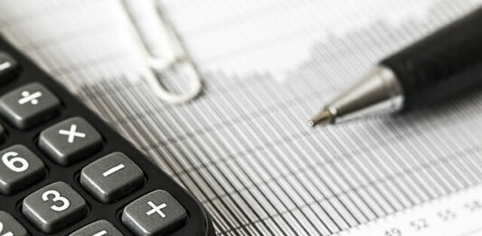 imagem contém papel de planilha, calculadora e caneta