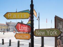 placas em um poste com nome de algumas cidades turísticas