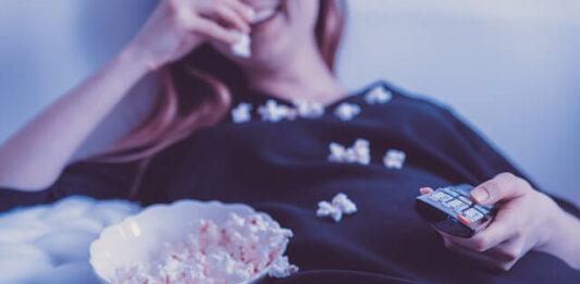 mulher deitada vendo filme e comendo pipoca