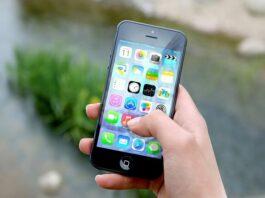 Mão segurando celular com apps