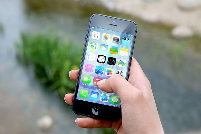 Foto de uma pessoa mexendo no celular Iphone para ilustrar o texto sobre o Pix, novo pagamento instantâneo