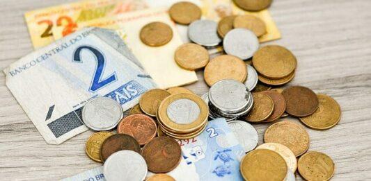 imagem contém várias notas e moedas de dinheiro