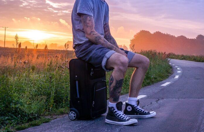 Homem sentado em cima da mala na estrada