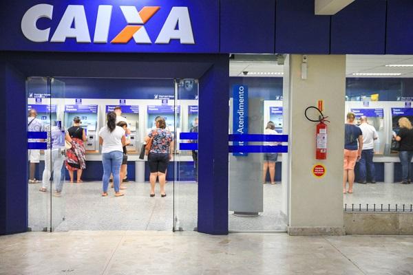 Imagem da faixada do banco Caixa Econômica Federal. Há pessoas dentro do banco. Imagem para ilustrar o texto sobre auxílio emergencial