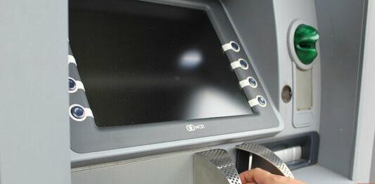 imagem de uma pessoa no caixa eletrônica realizando saque
