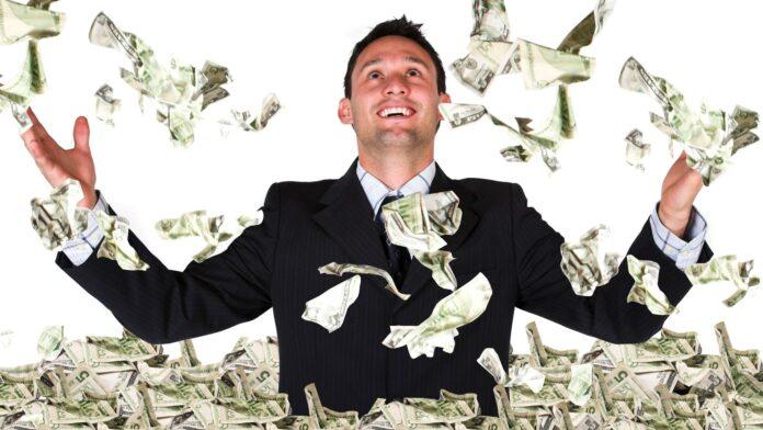 Homem de terno sorri e olha para o alto e notas de dinheiro voam ao seu redor