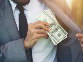 homem de terno colocando notas de dinheiro no bolso do paletó