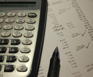imagem de uma planilha de contas e uma calculadora
