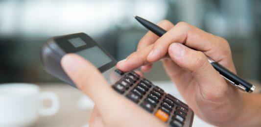 Mão com caneta preta usando calculadora