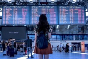 mulher morena de costas observando painel de embarque do aeroporto