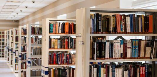 Fileira de estantes bege com muitos livros em uma biblioteca