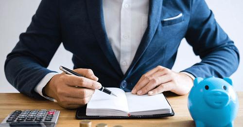 engravatado escrevendo em um caderno com um cofre azul e calculadora do lado