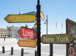 placas penduradas em um poste com nome das cidades mais famosas do mundo