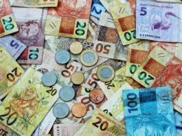 várias notas de reais espalhadas com moedas