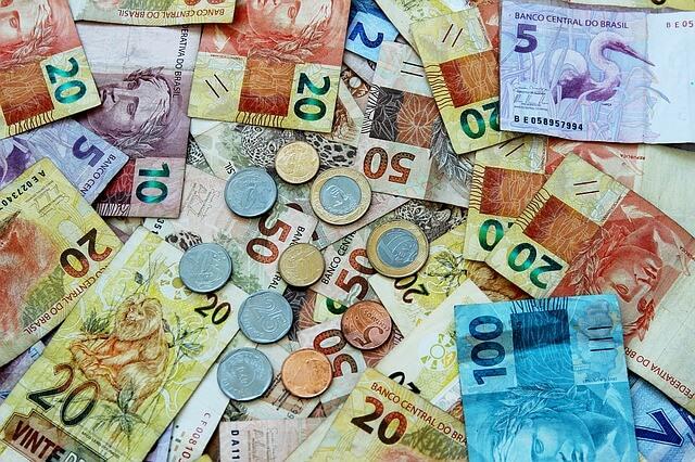 Imagem que contém notas de cinco, dez, vinte, cinquenta e cem reais para ilustrar o texto sobre auxílio emergencial de R$300