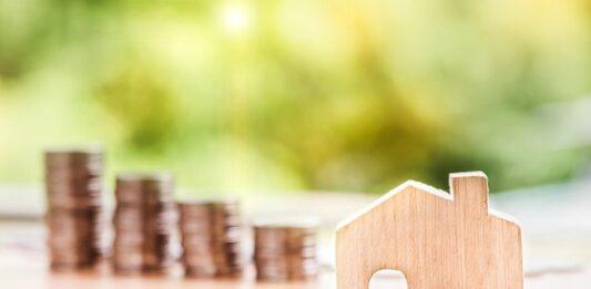 casa em miniatura com moedas empilhadas