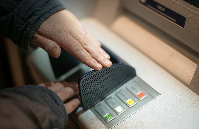 Pessoa utilizando um caixa eletrônico para saque de dinheiro