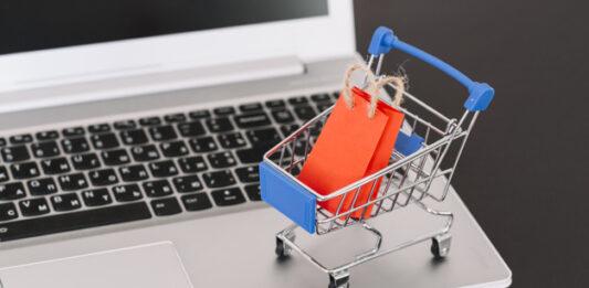 Notebook com carrinho de compra em miniatura carregando sacola de compra