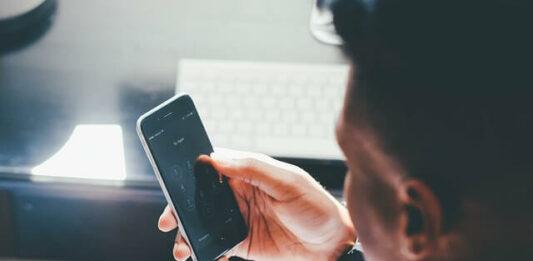Homem mexendo no celular para consultar as plataformas de afiliados