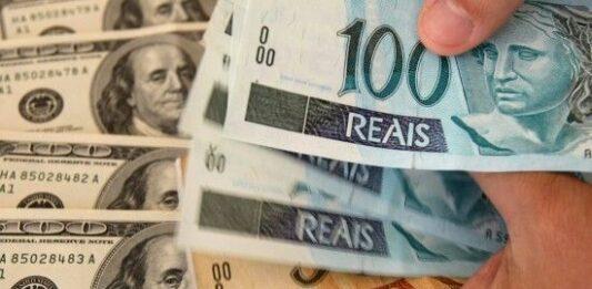 pessoa contado notas de real e de dólar