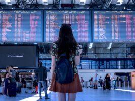 mulher parada em frente a um terminal de viagem