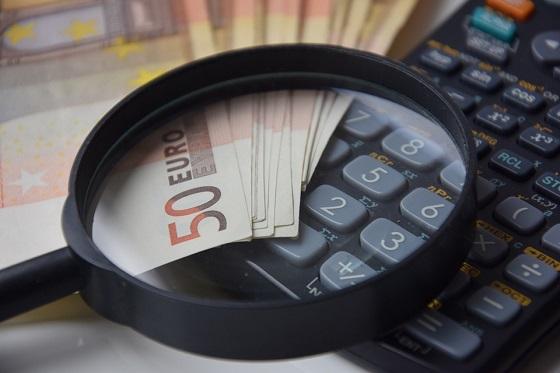 lupa em cima de notas de dinheiro e uma calculadora