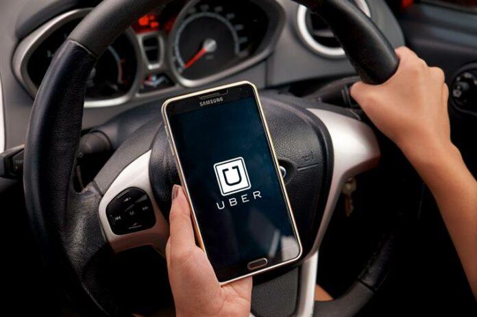 motorista de uber acessando aplicativo no celular com mão no volante