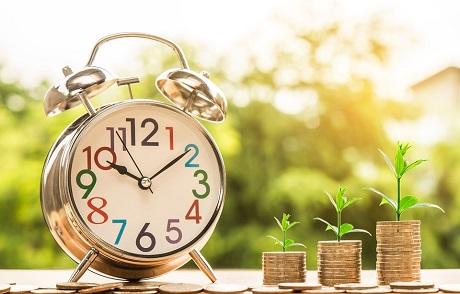 Relógio despertador ao lado de três fileiras de moedas