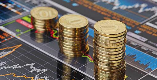 moedas empilhadas perto de gráficos de finanças
