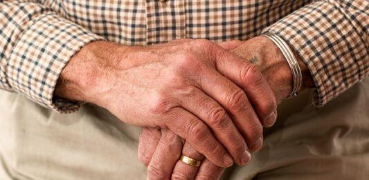 mão de um senhor de idade segurando uma bengala