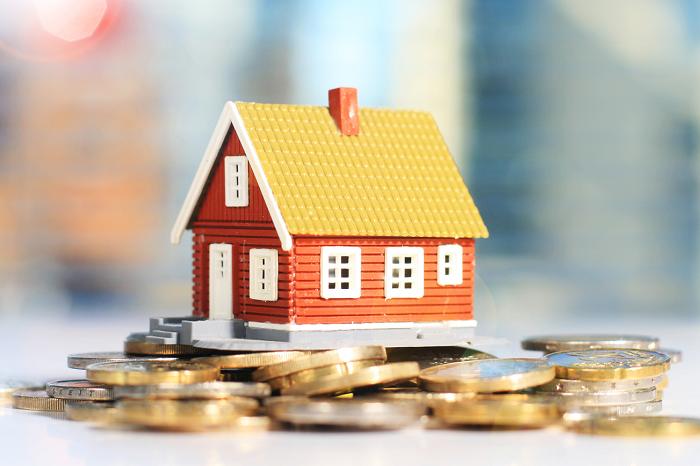 imagem de uma casa miniatura com várias moedas espalhadas em volta